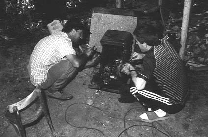 Omari and his neighbour fixing the generator.